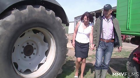 Mature couple hiding behind a tractor to fuck outdoors