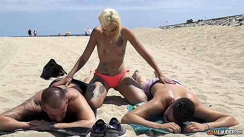 Silvana Violet touching two men on the public beach