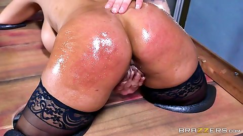 Bridgette B is oiled and locked in bondage device
