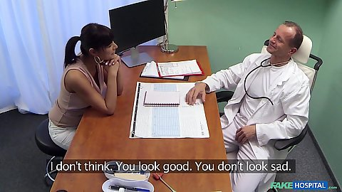 Doctor talks to female patient at his desk
