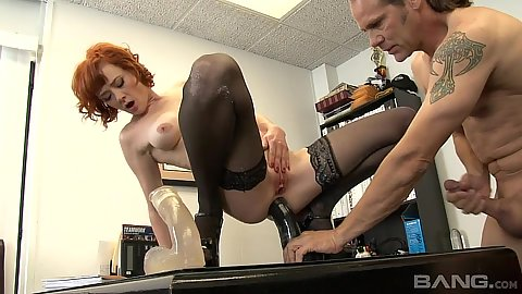 Giving redhead milf Audrey Hollander sits on a giant dildo on office table