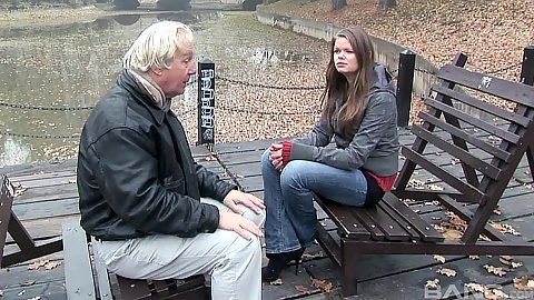 Old man and young girl talk on a bench in the park outdoors with Jenny Noel