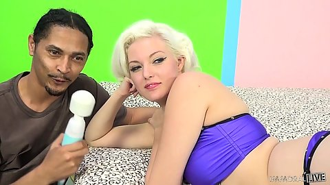 Flirting blonde interracial Jenna Ivory looks at a vibrator