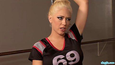 Blonde girl in sports jersy leans on stripper pole