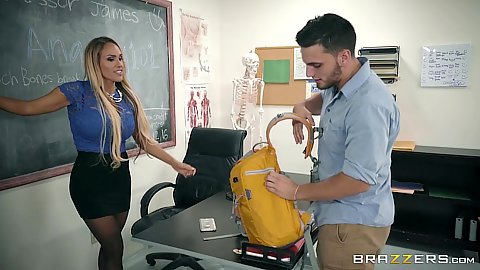 Classroom teacher in miniskirt Tegan James plays with toy at her desk