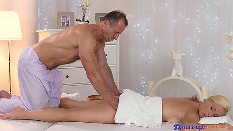 Naked blonde Nela Angel lays on massage table receiving gropign