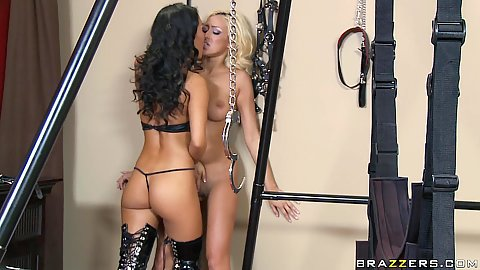 Two lesbians playing around a sex swing