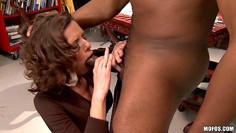 Milf on her knees deepthroating a large black cock