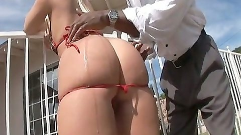 Riley Winter pulls down her bikini to get her big ass oiled up outdoors