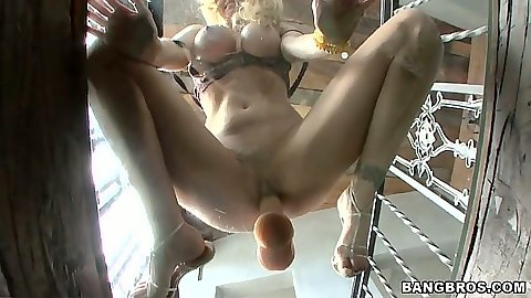Julia Ann sits on glass table with suction cup dildo