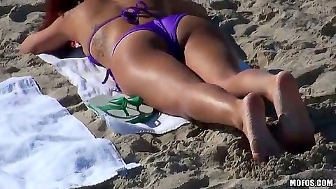 Nikki Chase tanning in bikini on a public beach outdoors solo
