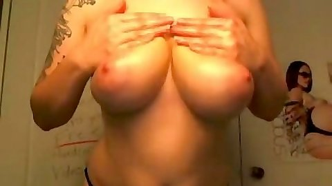 Busty emo girl attaching some piercing to her nipples
