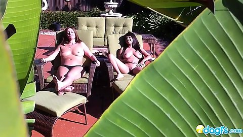 Outdoor voyeur shots of two lesbians sunbathing topless