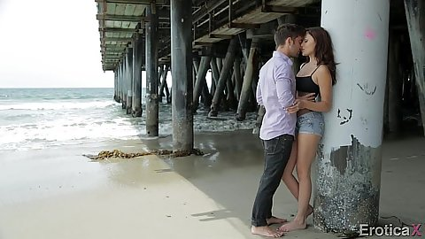Making out fully clothed under a bridge on the beach