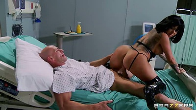 Doctor Julia Bond wearing boots and leather sitting on patients cock
