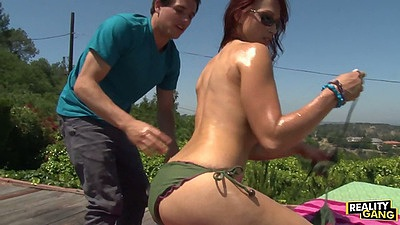 Spicy milf Nikki Hunter taking off her bikini and putting some oil on ass outdoors
