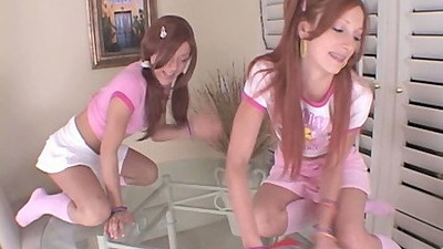 Redhead lesbian girls fucking around in miniskirts on glass table