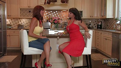 Fully clothed lesbians Carrie Ann and Desi Foxx having a chat in kitchen and undressing