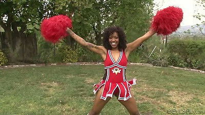 Ebony cheerleader outdoors in uniform with  Lotus Lain practicing her moves