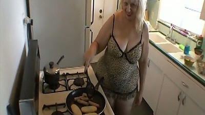 Mature mom or maybe a granny in bbw style cooks up some sausages on the stove